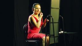 Een jonge vrouw in een rode kleding voor een spiegel zet een rode contour op haar lippen stock footage