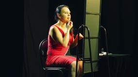 Een jonge vrouw in een rode kleding voor een spiegel zet een rode contour op haar lippen stock videobeelden