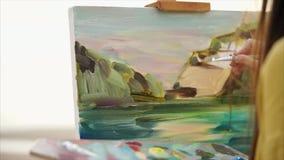 Een jonge vrouw schildert het schilderen op canvas, dat zich op een schildersezel bevindt stock video