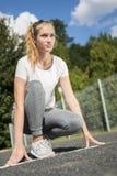 Een jonge vrouw in sportkleding knielt bij de beginnende lijn aan de looppas stock afbeeldingen