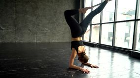 Een jonge vrouw in een sportkostuum, voert oefeningen voor flexibiliteit uit stock footage