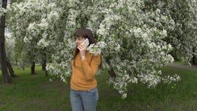 Een jonge vrouw spreekt op de telefoon naast een bloeiende appelboom stock video