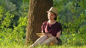 Een jonge vrouw in een strohoed en een kleding zit dichtbij een boom en gebruikt een tabletcomputer stock videobeelden