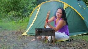 Een jonge vrouw in een T-shirt zit in het bos tegen een groene tent, draait de barbecue op haar barbecue algemeen plan stock videobeelden