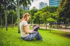 Een jonge vrouw in toevallige kleding die laptop in een tropisch park op de achtergrond van wolkenkrabbers met behulp van Mobiel  stock foto