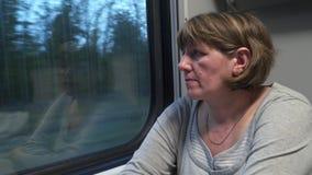 Een jonge vrouw in een treinauto kijkt uit het venster stock videobeelden