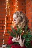 Een jonge vrouw verfraait een huis voor Kerstmis en een nieuw jaar Stock Afbeelding