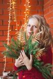 Een jonge vrouw verfraait een huis voor Kerstmis en een nieuw jaar Stock Foto's