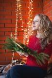 Een jonge vrouw verfraait een huis voor Kerstmis en een nieuw jaar Royalty-vrije Stock Foto