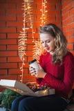 Een jonge vrouw verfraait een huis voor Kerstmis en Nieuwjaar Houdt een doos van speelgoed tegen de achtergrond van een bakstenen Stock Foto
