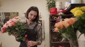 Een jonge vrouw verzamelde een bloemenboeket, toont zij bloemen aan stock footage