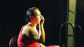 Een jonge vrouw voor een spiegel zet heldere oogschaduwwen op haar oogleden met een borstel stock video