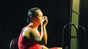Een jonge vrouw voor een spiegel zet op oogschaduwwen met een borstel stock footage
