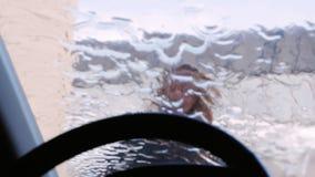 Een jonge vrouw wast haar auto in een zelfbedieningsgootsteen De mening van binnenuit de auto, de waterstraal op het windscherm stock video