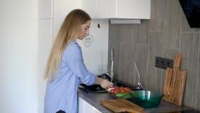 Een jonge vrouw wast verse groenten om een lichte salade van tomaten en komkommers te maken, die zij zal snijden stock video
