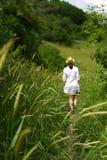 Een jonge vrouw in een witte kleding en een hoed loopt langs de weg onder de groene grassen stock fotografie
