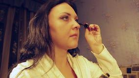 Een jonge vrouw in een witte laag rookt haar wimpers met mascara stock videobeelden