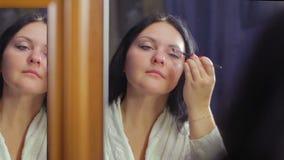 Een jonge vrouw in een witte laag voor een spiegel maakt oogmake-up met een kosmetische borstel stock videobeelden