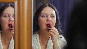 Een jonge vrouw in een witte laag voor een spiegel omringt kleurenlippen met heldere rode lippenstift stock video