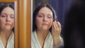 Een jonge vrouw in een witte laag voor een spiegel past kosmetische schaduwen op haar oogleden met een borstel toe stock footage