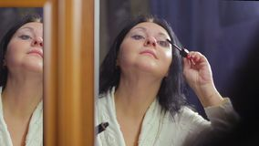 Een jonge vrouw in een witte laag voor een spiegel past mascara op haar wimpers toe stock video