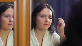 Een jonge vrouw in een witte laag voor een spiegel schildert de lagere wimpers met mascara stock footage
