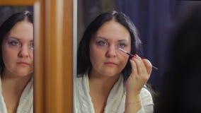 Een jonge vrouw in een witte laag voor een spiegel schildert haar ogen met schaduwen met een borstel stock videobeelden