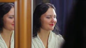 Een jonge vrouw in een witte robe voor een spiegel met heldere rode lippenstift glimlacht en flirt met haar lippen stock footage