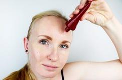 Een jonge vrouw zet een gelmasker op haar gezicht Zorg voor olieachtige, probleemhuid stock afbeeldingen