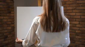 Een jonge vrouw zet op een schildersezel een tekenpapier Art Studio 4K langzame mo stock footage
