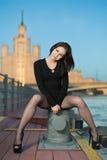 Een jonge vrouw zit op het apparaat voor de meertros van schip stock afbeeldingen