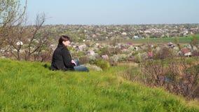 Een jonge vrouw zit op een heuvel en kijkt neer op het huis stock footage