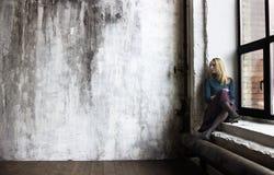 Een jonge vrouw zit op een vensterbank stock foto