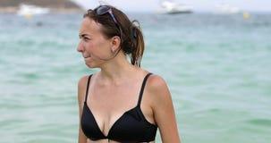 Een jonge vrouw in een zwart badpak kleedt zonnebril en drijft in het overzees stock videobeelden