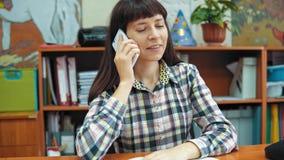Een jonge vrouwelijke leraar die op de telefoon in het kabinet spreken stock footage