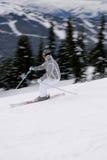 Een jonge vrouwelijke skiër die bergaf geniet van ski?end in Britse Columbi Stock Foto