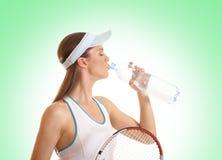 Een jonge vrouwelijke tennisspeler is drinkwater Stock Fotografie