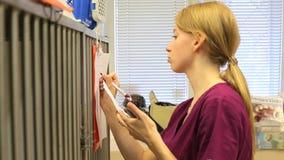 Een jonge vrouwelijke verpleegster in een dierenartskliniek schrijft op papier in een klembord, dat aan kooien voor dieren in bij stock footage