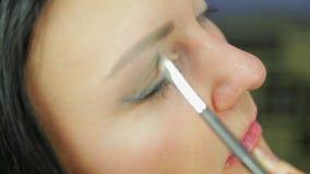 Een jonge vrouwen nangosit oogschaduw met een borstel profiel stock footage