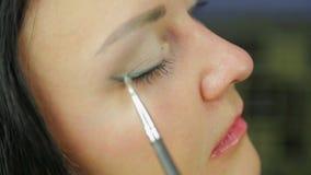 Een jonge vrouwen nangosit oogschaduw met een borstel profiel Close-up stock footage