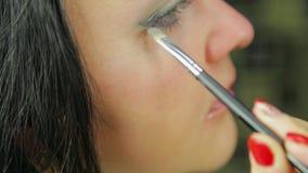 Een jonge vrouwen nangosit oogschaduwwen met een borstel profiel stock video