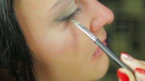Een jonge vrouwen nangosit oogschaduwwen met een borstel profiel stock footage