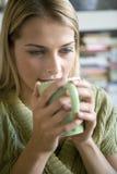 Een jonge vrouwen nippende koffie Stock Foto