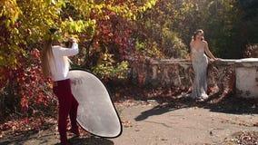 Een jonge vrouwenfotograaf neemt beelden van een model van het luxemeisje in de herfstpark stock video