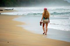 Een jonge vrouwengangen alleen op het strand Royalty-vrije Stock Afbeelding