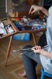 Een jonge vrouwenkunstenaar schildert een olieverfschilderij op de schildersezel royalty-vrije stock afbeeldingen