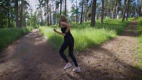 Een jonge vrouwenreeksen - dient een slim horloge op haar omhoog orde in om te weten hoeveel kilometers zij het park op warm door stock videobeelden