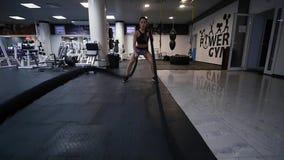Een jonge vrouwentreinen in een gymnastiek stock video