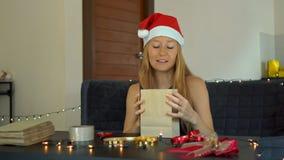 Een jonge vrouwenverpakking stelt voor Heden in ambachtdocument wordt verpakt met een rood en gouden lint voor Kerstmis of nieuw  stock videobeelden