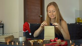 Een jonge vrouwenverpakking stelt voor Heden in ambachtdocument wordt verpakt met een rood en gouden lint voor Kerstmis of nieuw  stock footage
